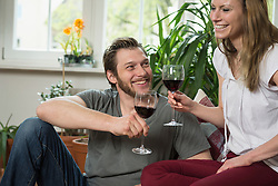 Couple drinking red wine in living room and smiling, Munich, Bavaria, Germany