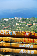 Section of graffiti covered safety fence, with small villages and Adriatic Sea in the background. Biokovo National Park, near Makarska, Croatia
