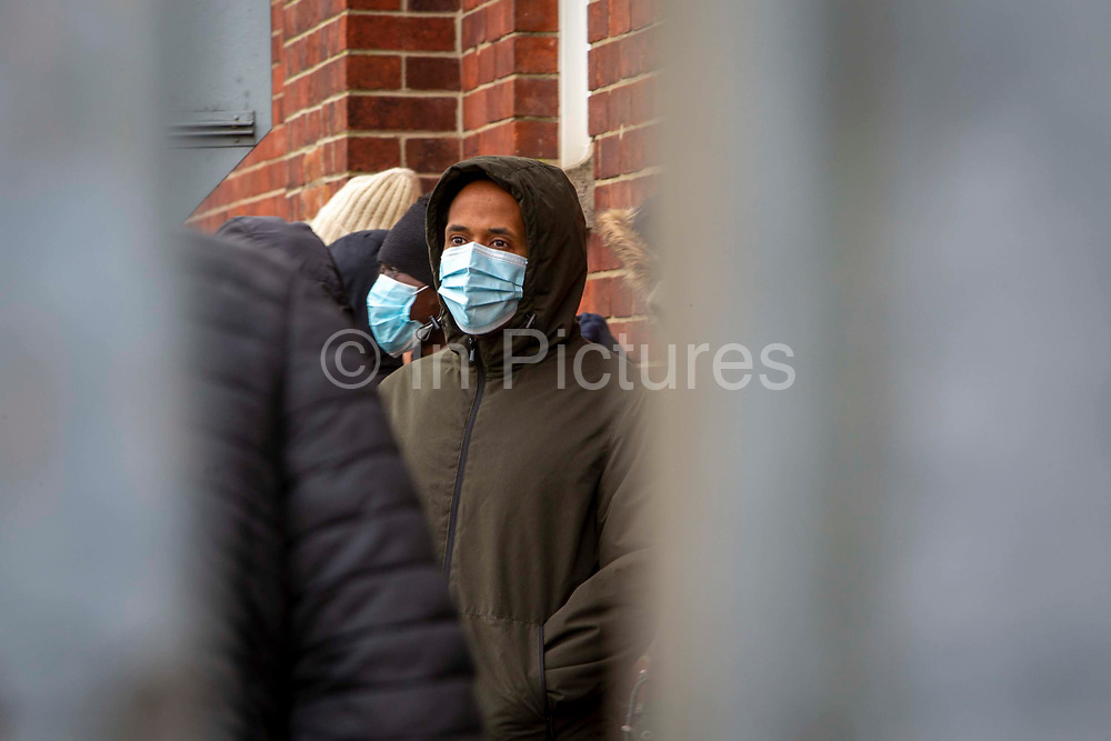 A young male Asylum seeker stands behind fencing and wears a mask inside Napier Barracks on the 12th of January 2021, Folkestone, United Kingdom. Over 400 asylum seekers are being kept at Napier Barracks in unsuitable, cold accommodation, they are experiencing mental health issues as well as being vulnerable to health conditions including COVID-19.