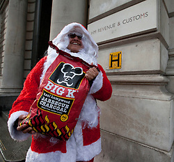 © Licensed to London News Pictures. 17/12/2011. LONDON, UK. A UK Uncut protester delivers coal, traditionally give by Father Christmas to children who have been bad, to HM Revenue and Customs (HMRC) on Whitehall London. The protest was carried out because of HMRC are currently whistleblower Osita Mba with prosecution for revealing details of possibly illegal deals which could cost the taxpayer up to GB£20 million . Photo credit: Matt Cetti-Roberts/LNP