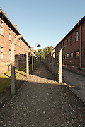 Space between the two barbed wire perimeter fences overlooked by a guard tower at Auschwitz I Extermination Camp