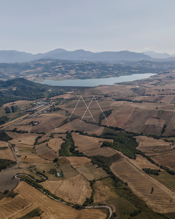Aerial view of countryside with Conza lake in background at sunset, Cairano, Irpinia, Avellino, Italy.