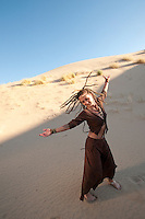 Unique woman dancing  freely outdoors with an open heart.