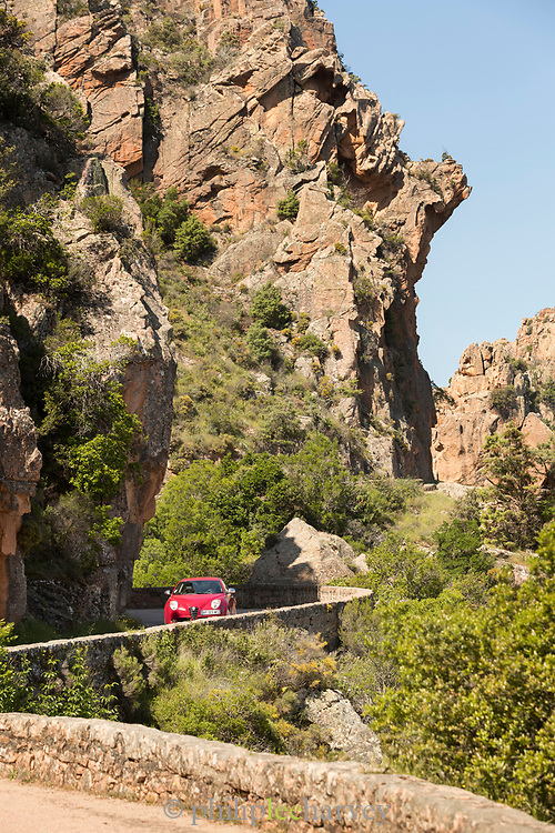 View of car on road on rocky cliff, Calanches de Piana, Corsica, France