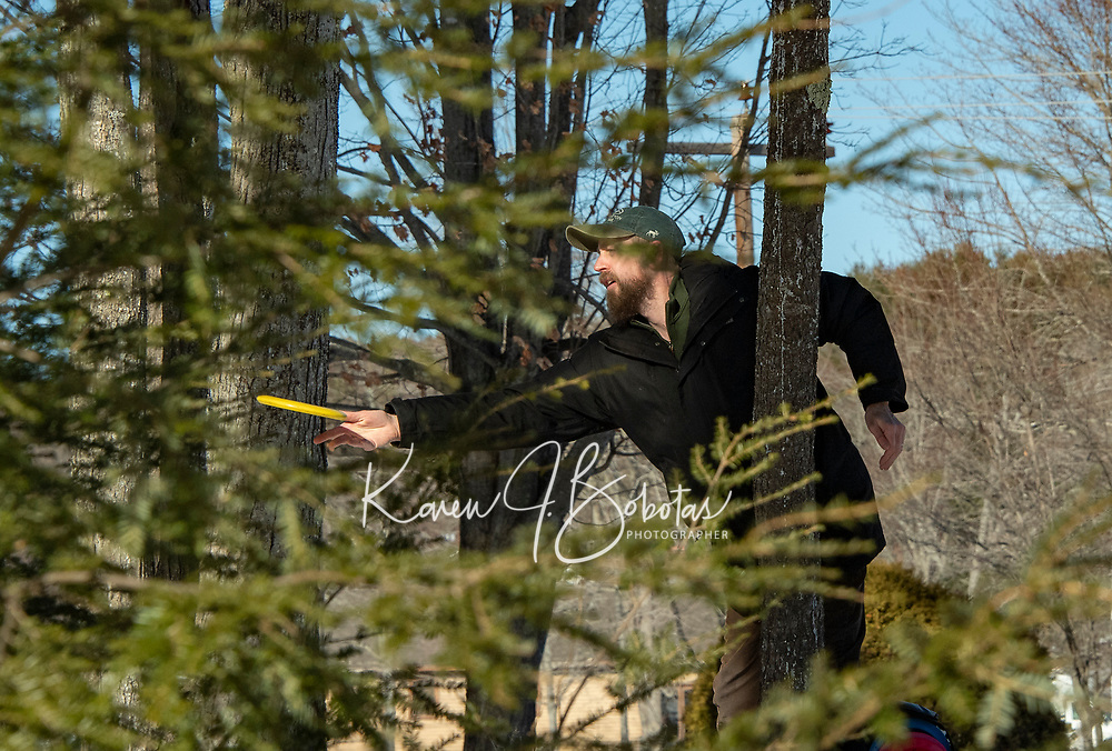 Scott Jarvis makes a chip shot from the trees at the Chris Daigle Memorial Disc Golf course at Bolduc Park Friday afternoon.  (Karen Bobotas Photo/for The Laconia Daily Sun)