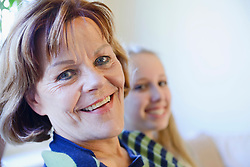 Portrait of grandmother and granddaughter, smiling, close up