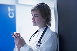Young female doctor text messaging on mobile phone in clinic, Freiburg im Breisgau, Baden-Wuerttemberg, Germany
