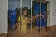 A boy looks through the window of a house flooded by mud in Paracatu de Baixo, one of the districts of Mariana, a brazilian city in the state of Minas Gerais. On november 5th, a mining waste dam failed causing a flood of mud.