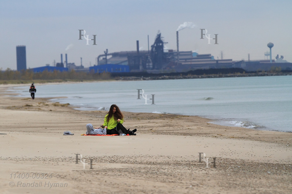 Couple lie on sandy Marquette Beach with industry in distance on chilly afternoon along Lake Michigan in late October; Gary, Indiana.