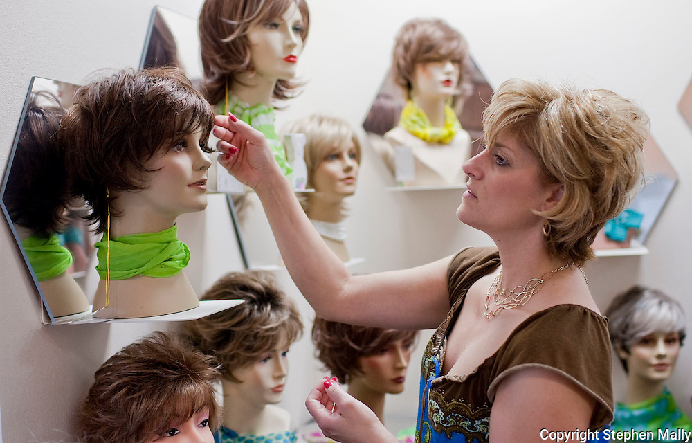 """D Vizecky, of Cedar Rapids, adjusts one of the many displays in the """"wig room"""" at Advanced Hair Technologies in Hiawatha on Saturday, May 29, 2010."""