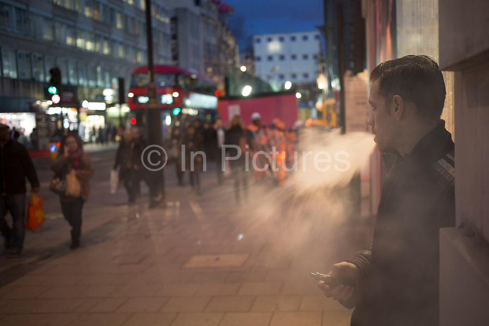 """Man smoking a vaporizer on Oxford Street in central London, UK. Britiains busiest shopping district. Electronic cigarettes  are battery-powered vaporizers that simulate the feeling of smoking, but without tobacco. Their use is commonly called """"vaping"""". Instead of cigarette smoke, the user inhales an aerosol, commonly called vapor."""