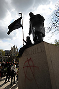 A protestor waves a black flag under a statue of Winston Churchill and opposite The Houses of Parliament during a May Day demonstration in Parliament Sqaure, London.