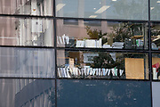Seen through the window of an office window, is an emplyee whose files, books and manuals lining their window sill at the premises of a corporate workplace in the City of London, the capital's financial district, on 21st September 2021, in London, England. Post-Covid pandemic, City workers are returning to their office desks in greater numbers but many still prefer to work from home for at least 1-2 days a week.