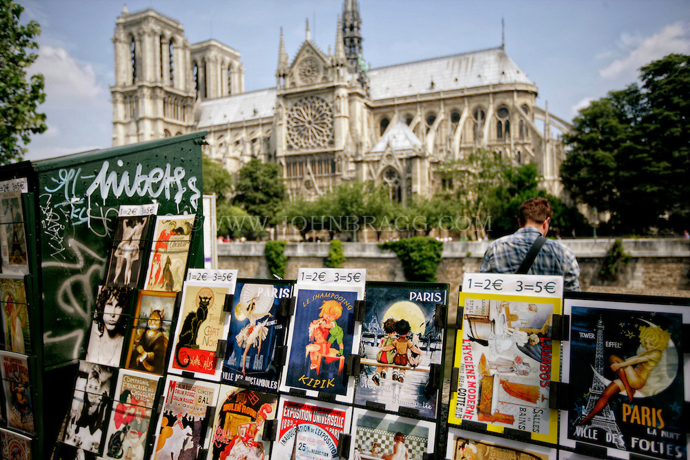 A Seine River Replica Poster stand with a view of Notre Dame Cathedral, Paris, France.