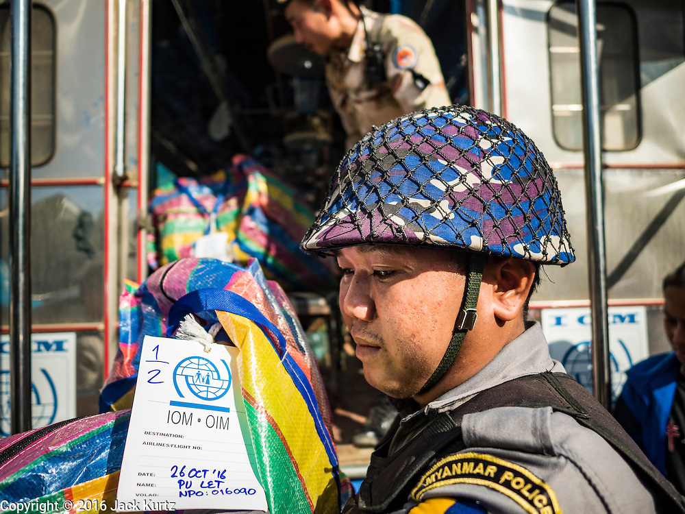 26 OCTOBER 2016 - MYAWADDY, KAYIN STATE, MYANMAR: A Myanmar police officer helps Myanmar refugees repatriated to Myanmar from Thailand. Sixtyfive Burmese refugees living in the Nupo Temporary Shelter refugee camp in Tak Province of Thailand were voluntarily repatriated to Myanmar. About 11,000 people live in the camp. The repatriation was the first large scale repatriation of Myanmar refugees living in Thailand. Government officials on both sides of the Thai / Myanmar border said the repatriation was made possible by recent democratic reforms in Myanmar. There are approximately 150,000 Burmese refugees living in camps along the Thai / Myanmar border. The Thai government has expressed interest several times in the last two years in starting the process of repatriating the refugees.     PHOTO BY JACK KURTZ