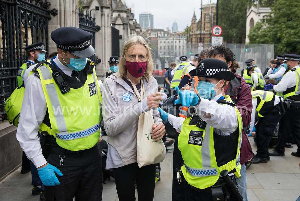 Metropolitan Police officers detain a climate activist from Extinction Rebellion who had occupied the pavement outside the Houses of Parliament on 3 September 2020 in London, United Kingdom. Extinction Rebellion activists are attending a series of September Rebellion protests around the UK to call on politicians to back the Climate and Ecological Emergency Bill (CEE Bill) which requires, among other measures, a serious plan to deal with the UK's share of emissions and to halt critical rises in global temperatures and for ordinary people to be involved in future environmental planning by means of a Citizens' Assembly.