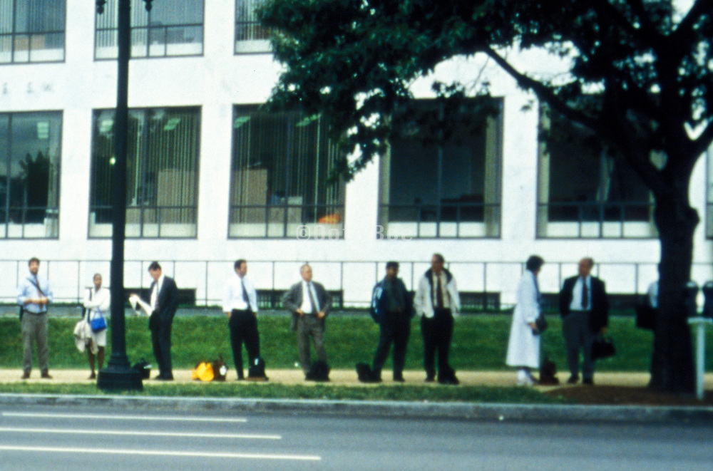 line of commuters waiting for the bus
