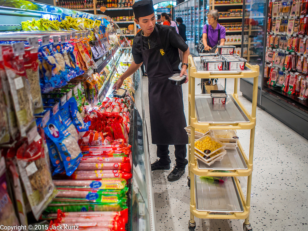 """27 MARCH 2015 - BANGKOK, THAILAND: A worker stocks shelves in Gourmet Market, a grocery store, in """"EmQuartier,"""" a new mall in Bangkok. """"EmQuartier"""" is across Sukhumvit Rd from Emporium. Both malls have the same corporate owner, The Mall Group, which reportedly spent 20Billion Thai Baht (about $600 million US) on the new mall and renovating the existing Emporium. EmQuartier and Emporium have about 450,000 square meters of retail, several hotels, numerous restaurants, movie theaters and the largest man made waterfall in Southeast Asia. EmQuartier celebrated its grand opening Friday, March 27.   PHOTO BY JACK KURTZ"""
