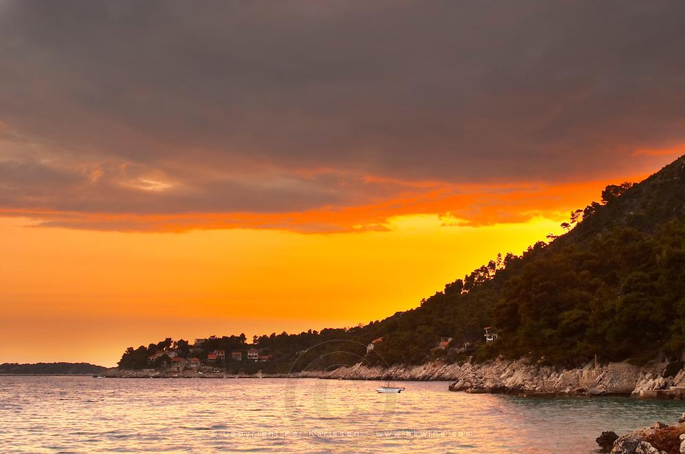 The Brna bay at sunset, bright orange sky, sky reflected in the sea water. Holiday homes on the hillside. Bright orange fiery sky. Prizba village. Korcula Island. Prizba, Riva Apartments, Danny Franulovic. Korcula Island. Dalmatian Coast, Croatia, Europe.
