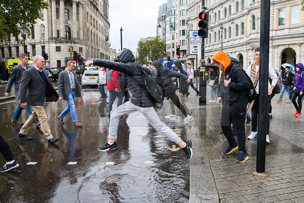 © Licensed to London News Pictures. 27/09/2019. London, UK. People are seen leaping over puddle of water in Westminster caused by heavy downpour in London. According to the Met Office, this weekend is set to be washout with over 2o hours of rainfall in the capital. Photo credit: Dinendra Haria/LNP. Photo credit: Dinendra Haria/LNP