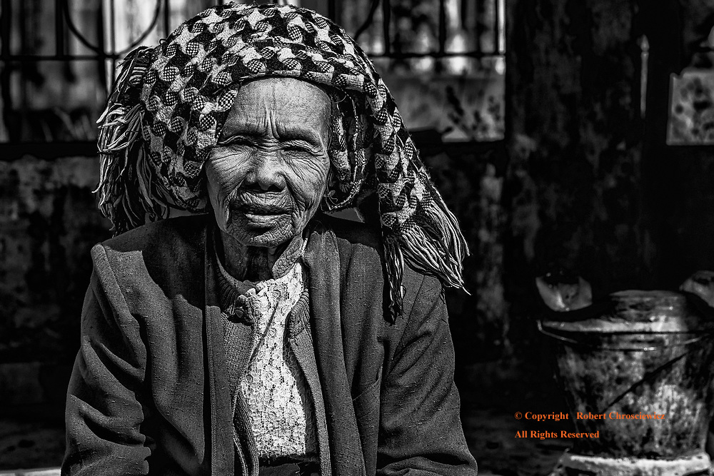 An older woman wears both thanaka on her face and her head dress as she pauses from her kitchen chores, Inle Lake Myanmar.
