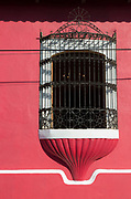 View of the detail of a window with a metal grate in a red wall, Leon, Nicaragua