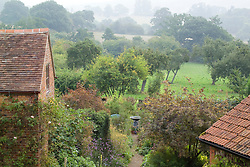 General view of the garden and countryside beyond on a misty autumn morning
