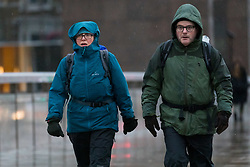 © Licensed to London News Pictures. 01/12/2018. London, UK.  A coupole walking walk across London Bridge during rain and wet weather on the first day of meteorological winter.  Photo credit: Vickie Flores/LNP