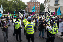 London, UK. 3rd September, 2020. Climate activists from Extinction Rebellion stand outside 10 Downing Street during a 'Carnival of Corruption' protest against the government's facilitation and funding of the fossil fuel industry. Extinction Rebellion activists are attending a series of September Rebellion protests around the UK to call on politicians to back the Climate and Ecological Emergency Bill (CEE Bill) which requires, among other measures, a serious plan to deal with the UK's share of emissions and to halt critical rises in global temperatures and for ordinary people to be involved in future environmental planning by means of a Citizens' Assembly.