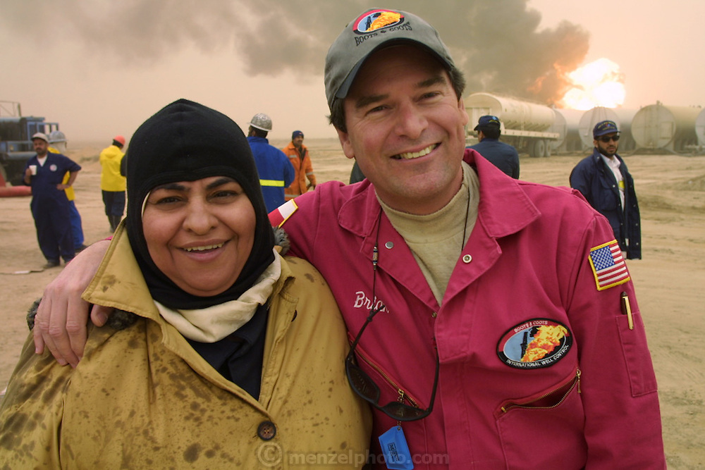 "Brian Krause, president of Boots and Coots, with Sara Akbar, development specialist for the Kuwait Oil Company and member of the firefighting team from the company's (KWWK: Kuwait Wild Well Killers) as they prepare to extinguish the first oil well fire in Iraq's Rumaila Oil field. Sara is a Muslim woman and is rather surprised by the way Brian, a friendly American, reacts to a photo by putting his arm around her. The other Kuwaiti's notice this too. After dousing the flames with high pressure water hoses, they sealed the spurting well of gas and oil with drilling mud using what is called a ""stinger,"" a tapered pipe on the end of a long steel boom controlled by a bulldozer. Drilling mud, under high pressure, is pumped through the stinger into the well, stopping the flow of oil and gas. The Rumaila oil field is one of Iraq's biggest with five billion barrels in reserve. Many of the wells are 10,000 feet deep and produce huge volumes of oil and gas under tremendous pressure, which makes capping them very difficult and dangerous. Rumaila is also spelled Rumeilah."