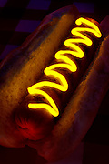 A glowing, curvacious line of yellow mustard illuminates a hot dog.Black light