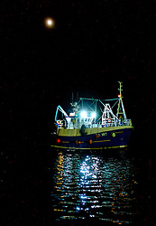 A fishing vessel returns to port by moonlight in Tobermory, Isle of Mull, Scotland<br /> <br /> (c) Andrew Wilson | Edinburgh Elite media