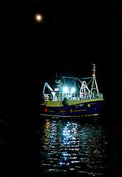 A fishing vessel returns to port by moonlight in Tobermory, Isle of Mull, Scotland<br /> <br /> (c) Andrew Wilson | Edinburgh Elite media