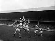 National Football League Semi-Final, Kerry v Down, Croke Park, Dublin...John Dowling, Kerry Full Forward jumps for the ball as it comes towards the Down goal and gets possession despite attention of two Down Backs. G. McMahon (no. 13) Kerry Left Full Forward is also in the picture...10.4.60