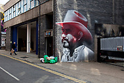 Photo realasitic cowboy painting by LA based graffiti artist El Mac. Street art in the East End of London is an ever changing visual enigma, as the artworks constantly change, as councils clean some walls or new works go up in place of others. While some consider this vandalism or graffiti, these artworks are very popular among local people and visitors alike, as a sense of poignancy remains in the work, many of which have subtle messages.