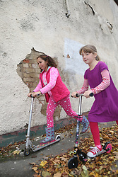 Girls playing on scooters in street