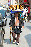 Typical Simitci Turkish man selling simit - turkish sesame bread rings in streets of Istanbul, Republic of Turkey