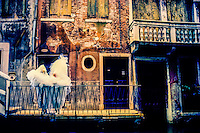 People in costume standing along a back canal during Carnevale (Carnival), Venice, Italy