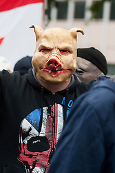 """Rotherham England<br /> 13 September 2014 <br /> EDL supporter wears a pig mask during a march from Rotherham Town Hall  to Rotherham Main Street Police station where they held a rally as part of the English Defence Leagues """"Justice for the Rotherham 1400"""" March described by an EDL Facebook Page as """"a protest against the Pakistani Muslim grooming gangs"""" on Saturday Afternoon <br /> <br /> <br /> Image © Paul David Drabble <br /> www.pauldaviddrabble.co.uk"""