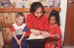 Teacher reading story book to nursery school children,