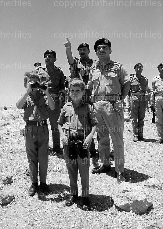 King Hussein of Jordan with sons Prince Abdullah and Prince Feisal seen watching an army exercise in the Jordanian desert in 1969. Photographed byTerry Fincher