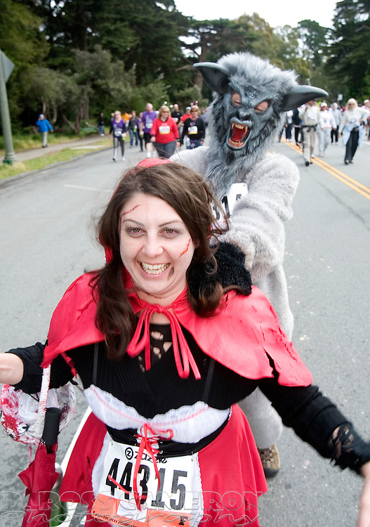 Little Red Riding Hood, aka Charlene Mitchell of Sacramento, doesn't escape the Big Bad Wolf (Allison Bendtson of Sacramento) as they pass through Golden Gate Park during the 100th running of the Bay to Breakers 12K in San Francisco, Sunday, May 15, 2011. (Photo by D. Ross Cameron)
