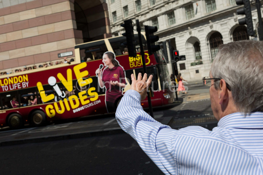 A man waves at a passing tour bus driving along Queen Victoria Street in the City of London, the capitals financial district aka the Square Mile, on 22nd August 2019, in London, England.