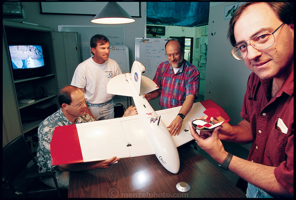 AeroVironment engineers (left to right) Marty Spadaro, Paul Trist Jr., Tom DeMarino, and Carlos Miralles cluster around the working prototype of the Mars glider, Otto. NASA sees an airplane as an important tool for exploring Mars early in the 21st century, and AeroVironment is seeking the honor of building the plane. From the book Robo sapiens: Evolution of a New Species, page 158 top.