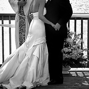 A couple kisses after tying the knot during their wedding ceremony on the Charleston harbor in this black and white photo. ©Travis Bell Photography