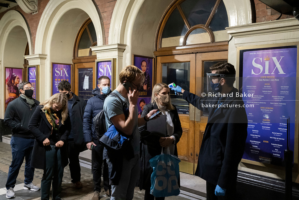 As Prime Minister Boris Johnson announces a second Coronavirus nationwide lockdown during the second wave of the pandemic, staff check customer body temperatures outside the Apollo Theatre on Shaftesbury Avenue where Adam Kay's medical comedy 'This Is Going To Hurt' is playing, on 31st October 2020, in London, England. But business such as theatres will again have to close from Thursday, and for a period of at least one month.