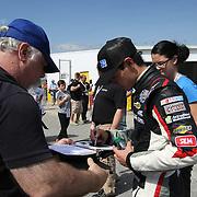 Clorox Chevrolet driver Kyle Larson signs autographs during a NASCAR Drive4COPD Nationwide Series practice session at Daytona International Speedway on Thursday, February 21, 2013 in Daytona Beach, Florida.  (AP Photo/Alex Menendez)