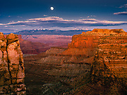 Sunset light warms the sandstone cliffs at The Neck, in Canyonlands National Park, as a full moon rises over the LaSal Mountains to the east.
