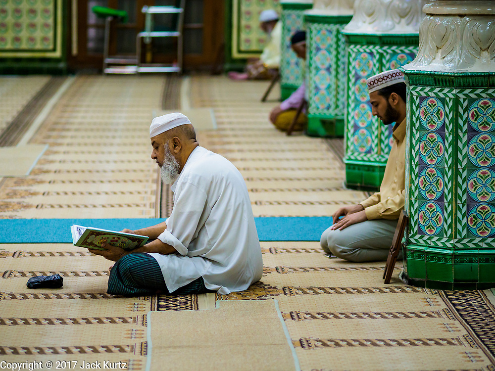 """24 NOVEMBER 2017 - YANGON, MYANMAR: Men pray in Surtee Sunni Jumma Mosque in Yangon. Many Muslims in overwhelmingly Buddhist Myanmar feel their religion is threatened by a series of laws that target non-Buddhists. Under the so called """"Race and Religion Protection Laws,"""" people aren't allowed to convert from Buddhism to another religion without permission from authorities, Buddhist women aren't allowed to marry non-Buddhist men without permission from the community and polygamy is outlawed. Pope Francis is to arrive in Myanmar next week and is expected to address the persecution of the Rohingya, a Muslim ethnic minority in western Myanmar. Some Muslims and Christians are concerned that if the Pope's comments take too strong of pro-Rohingya stance, he could exacerbate religious tensions in the country.  PHOTO BY JACK KURTZ"""