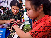 """13 JANUARY 2018 - BANGKOK, THAILAND:      A Thai army nurse uses theatrical makeup to put a simulated combat wound on a girl during Children's Day activities at the Royal Thai Army's King's Guard 2nd Cavalry Camp in central Bangkok. Children's Day is called """"Wan Dek"""" in Thai. Many government offices and military bases hold special activities for children as do shopping malls.  PHOTO BY JACK KURTZ"""